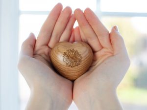A small three dimensional oak heart that splits in half to hold ashes or keepsakes with engraving on the front and back