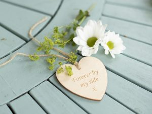 A thin wooden tag in the shape of a heart with twine threaded through the top